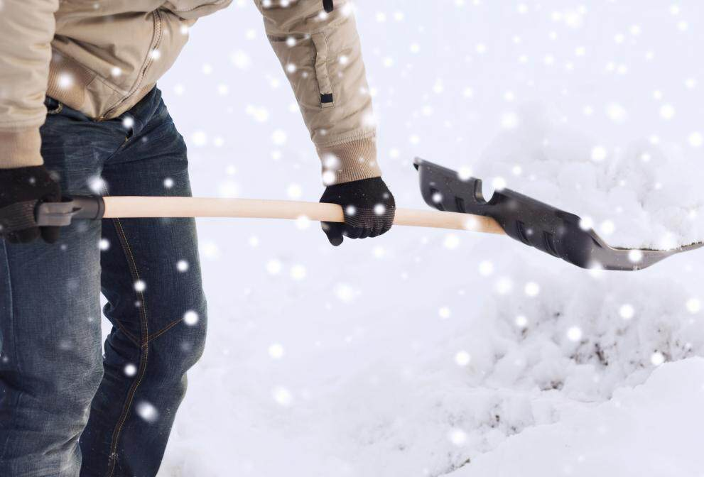 A Man Digging Snow with a Shovel